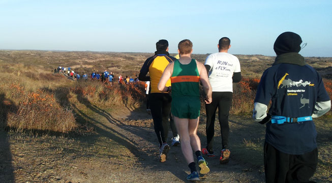 KLM Beach race with a stream of runners runing up and down and round the dunes
